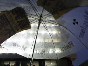 雨に濡れる傘、バックは原子力安全委員会のある庁舎